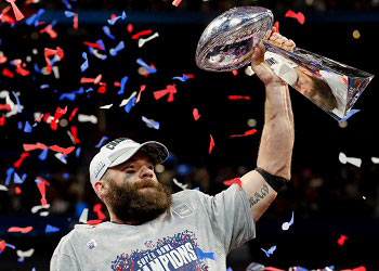 The National Football League's New England Patriots player, Julian Edelman, holding up the Super Bowl Lombardi trophy