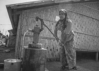 In honor of 2017 Genesis Prize Laureate Anish Kapoor, The Genesis Prize Foundation gave grants to six organizations helping alleviate the refugee crisis around the world. This image depicts a woman in Myanmar pumping clean water from a life-saving well that provides water access to the Rohingya ethnic group.